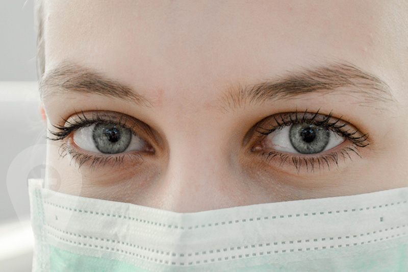 A pair of eyes of a vaccine provider wearing a face mask to protect against COVID virus