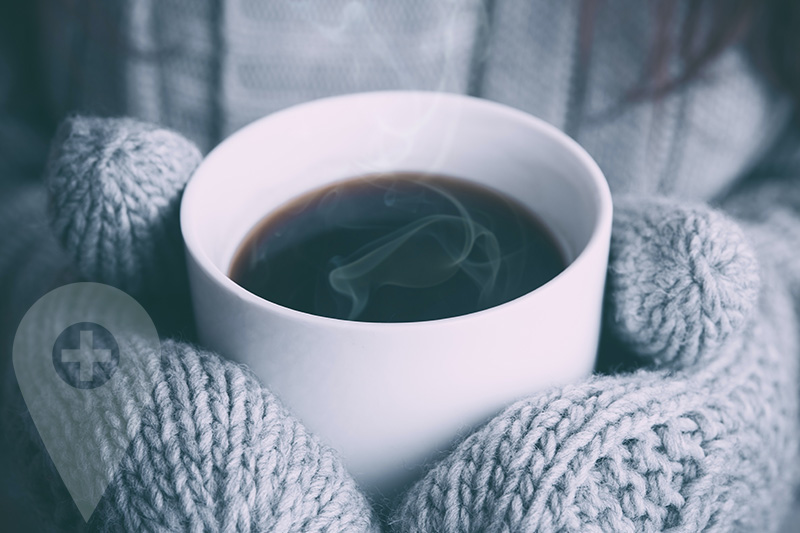 A person with woollen gloves holding a hot cup of black coffee
