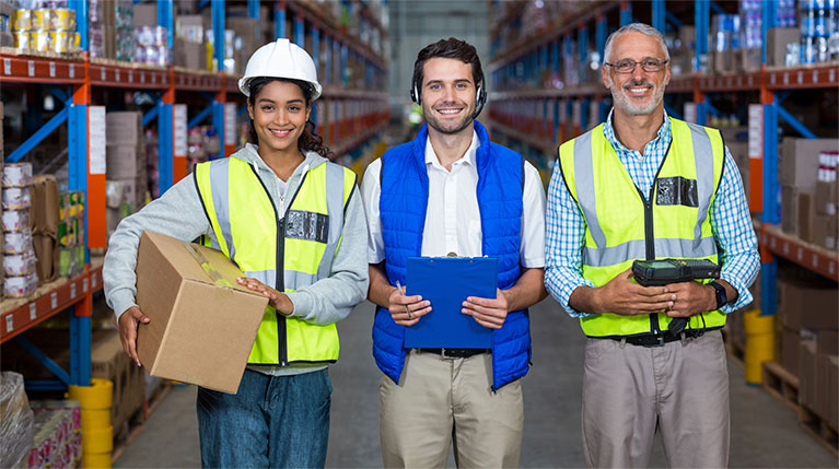 Three employees in a warehouse smiling